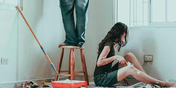 mand og kvinde maler hjem vægge med hvid maling